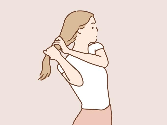 髪を手で持つ女性