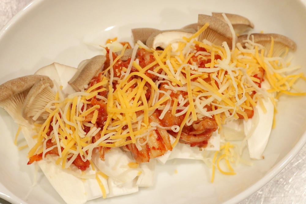 耐熱皿にエリンギ、キムチ、ピザ用チーズをのせて、しょうゆをかける