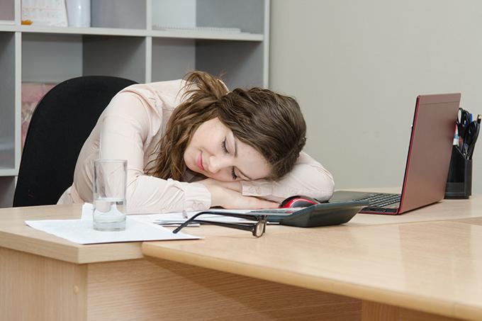 仕事中に昼寝する女性