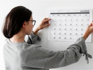 カレンダーを壁に貼る女性