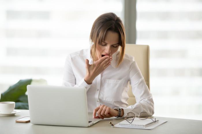 デスクワーク中あくびをしながら腕時計を見ている女性