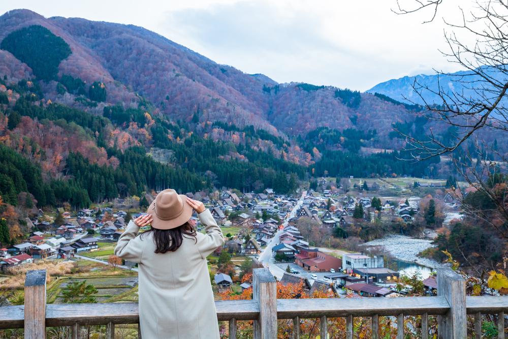 山に囲まれる家を見ている女性の後ろ姿