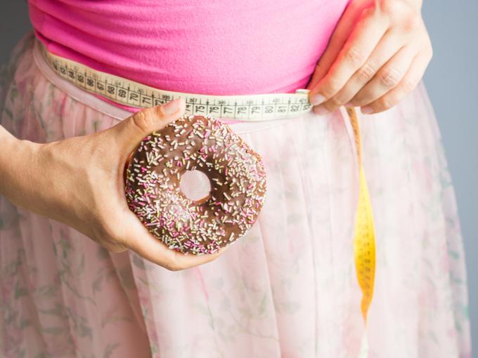 ウエストにメジャーを巻き、ドーナツを手に持つ女性