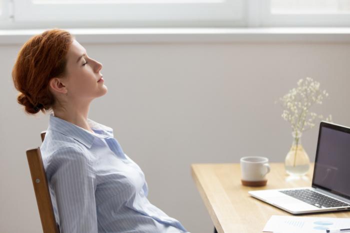 椅子に座って目を閉じリラックスしている女性