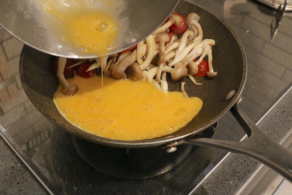 フライパンの空いたスペースにたまごを流し入れスクランブルエッグを作る