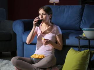 夜中にスナック菓子を食べる女性