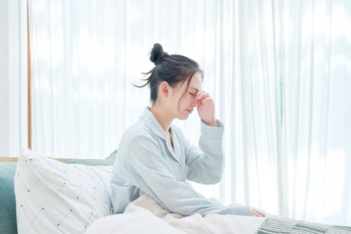 寝起き目もとに手を当てている女性