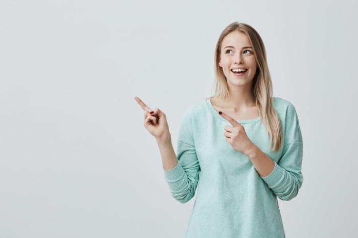 向かって左を両手で指す女性画像