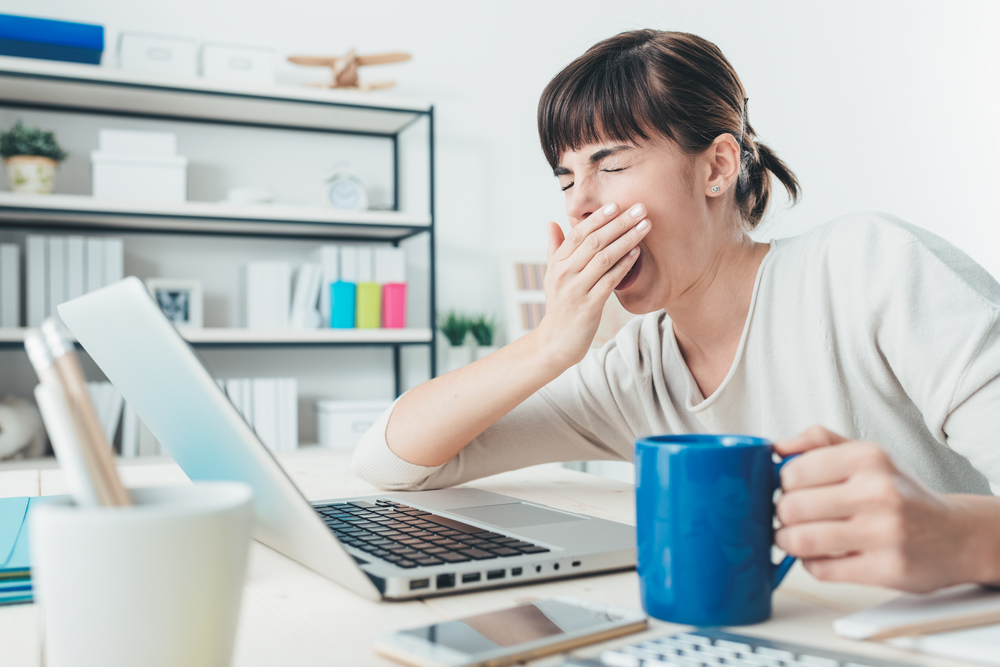 デスクワーク中、あくびをしている女性