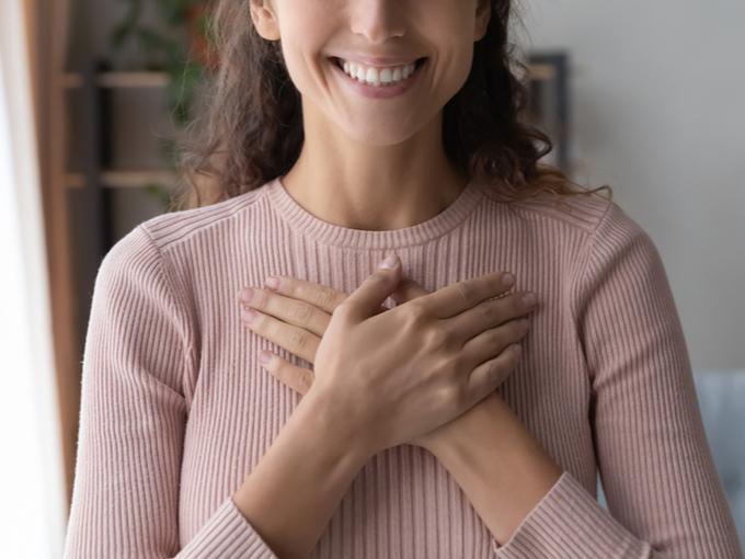 胸に手を当てる笑顔の女性