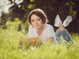 原っぱで読書をする女性