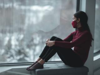 窓の外を眺めるマスク姿の女性