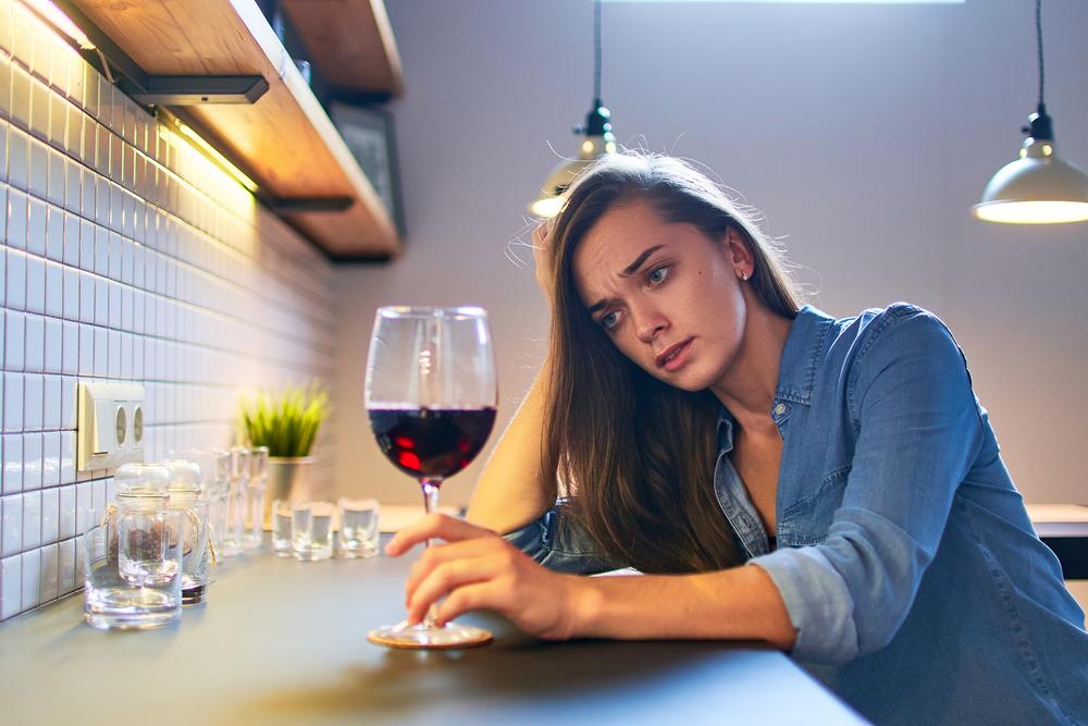 ワインの入ったグラスを眺めている女性