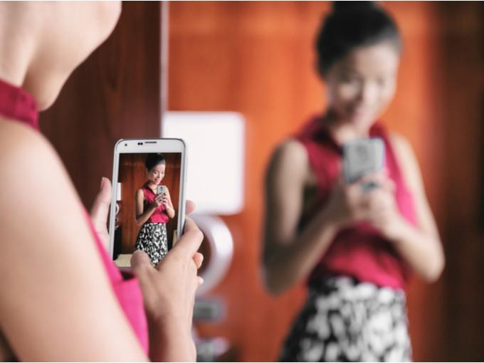 ケイタイの御カメラで自撮りする女性