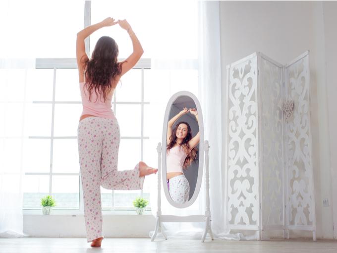 朝、鏡の前で笑顔の女性