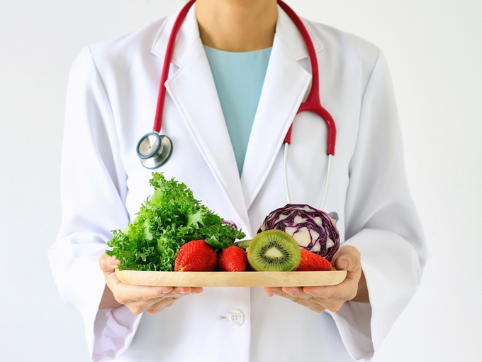野菜やフルーツのプレートを持った医師