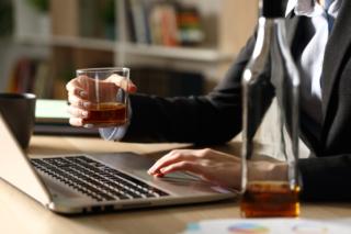 アルコールを片手にパソコン作業をしている女性の手もと