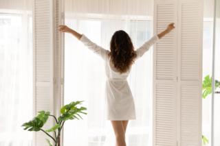 朝起きて窓から日差しを浴びている女性