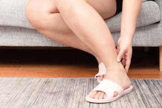 足首を押さえる女性の画像