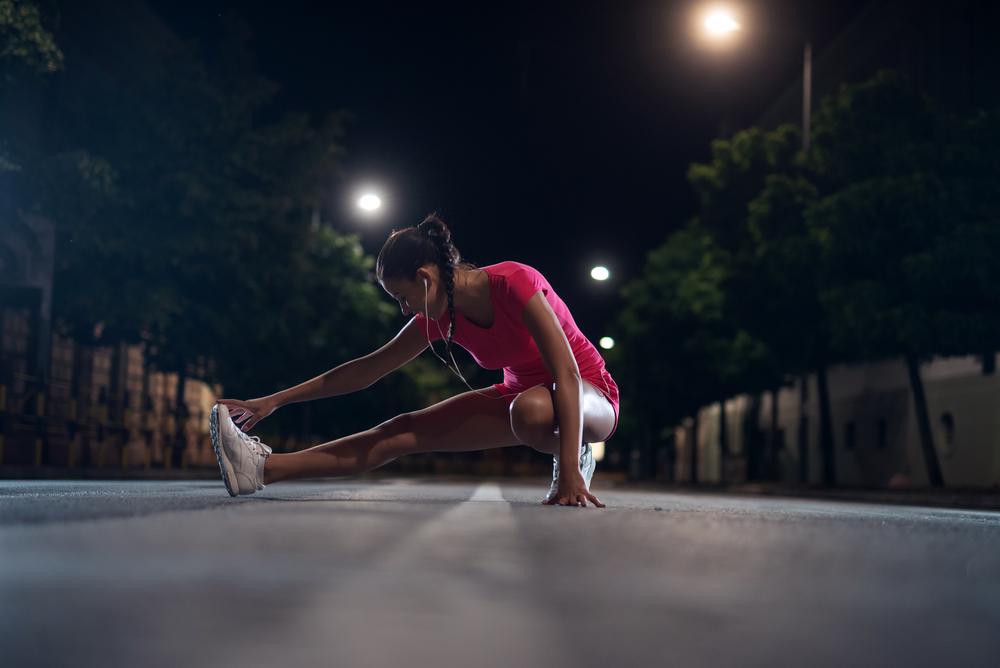 夜に運動する前のストレッチをしている女性