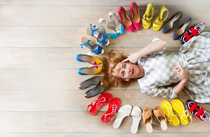 いろいろな色の靴に囲まれた女性の画像