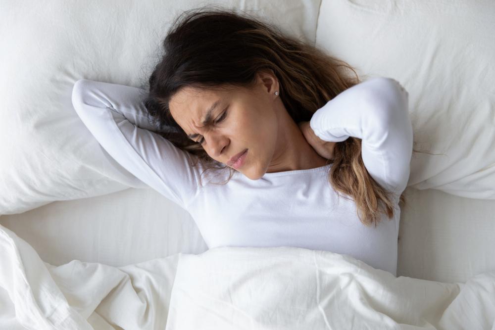 首あたりを抑えている寝苦しそうな女性