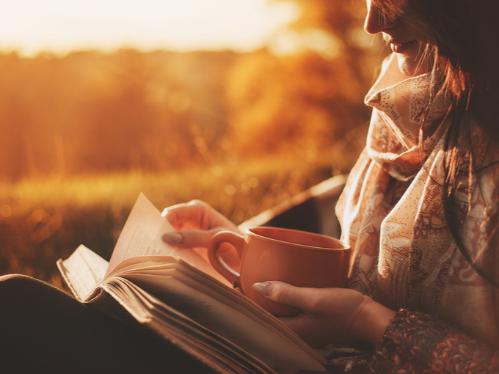 秋の公園で読書する女性